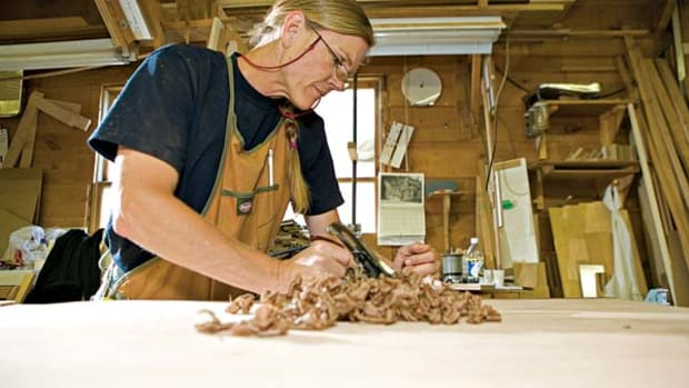 Kristen Terpening hand planes a red birch table's walnut trim, but there's a big, new, top-of-the-line Italian power planer for other tasks.