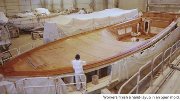 Workers finish a hand-layup in an open mold.