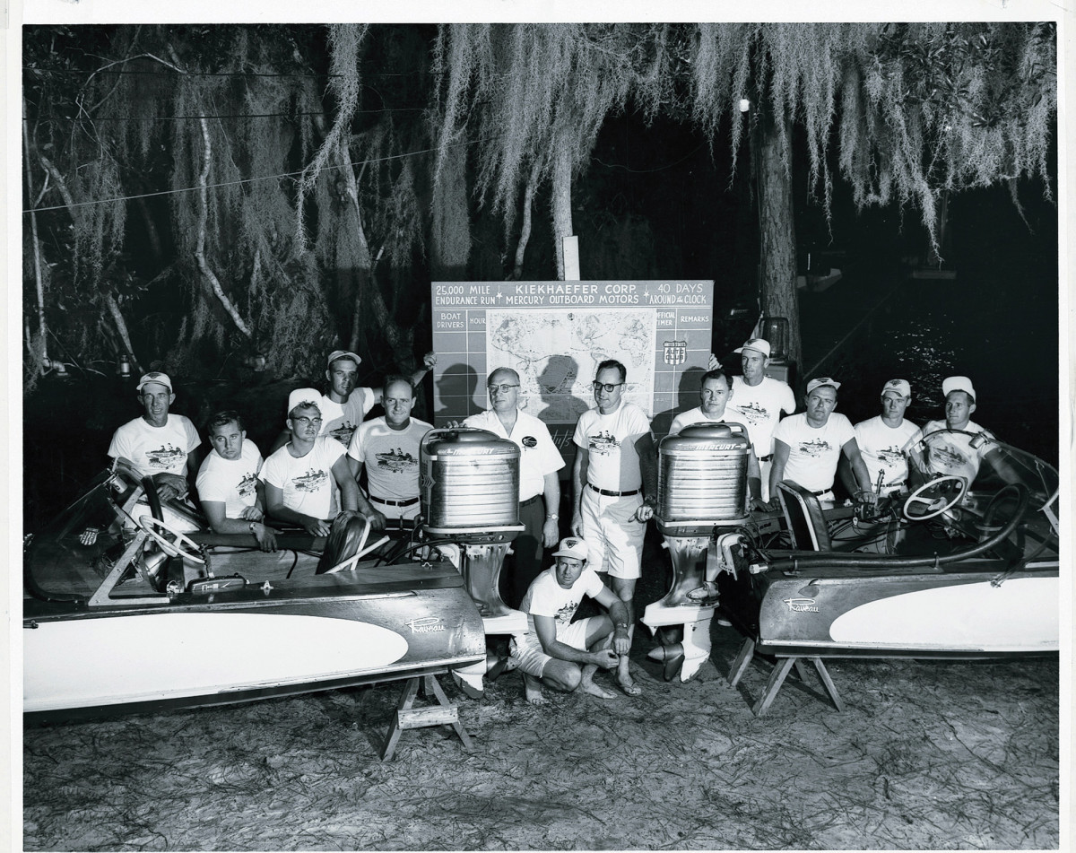 "Founder of Mercury Marine, legendary Carl Kiekhaefer (with hand on Mark 75 outboard), stands with ""his boys,"" the crew at top-secret Lake X."