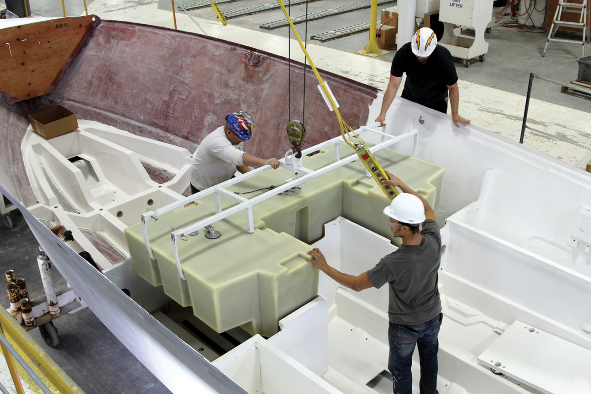 Workers at Tiara Yachts install a plastic fuel tank in a new 38 LS.