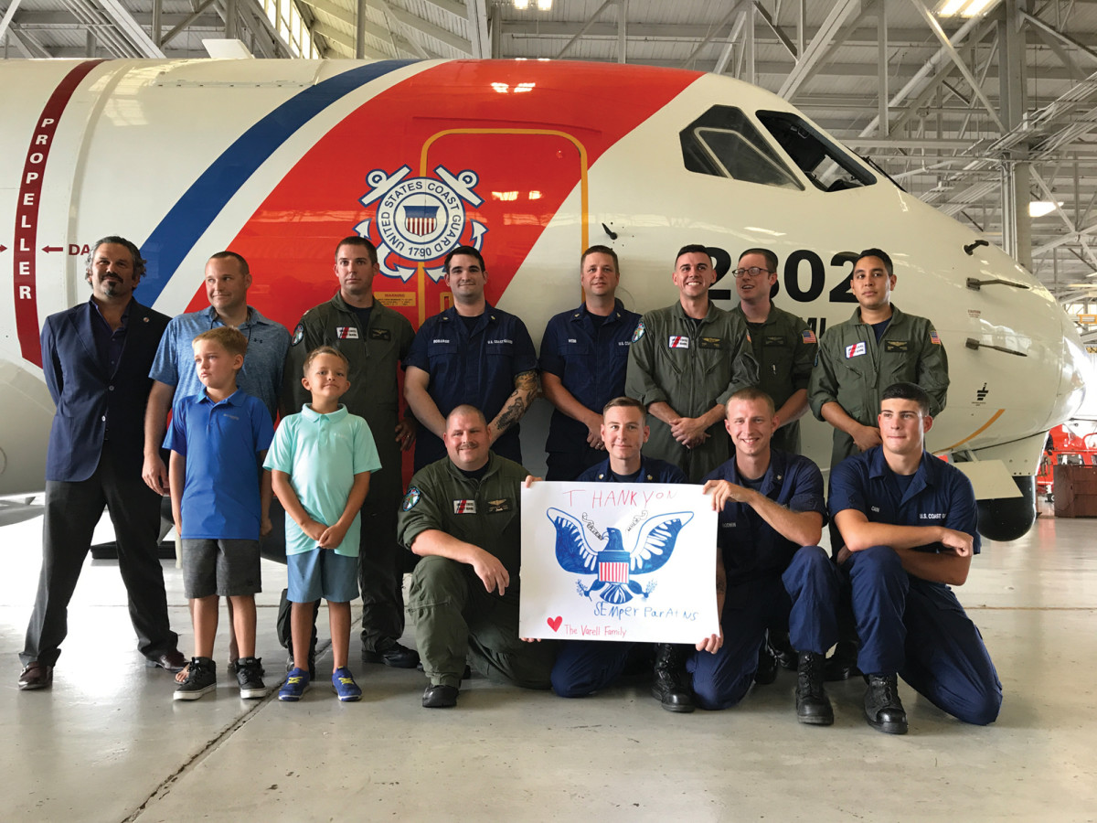 Geoff Varell with his sons Gregory, Grayden and the Coast Guard team that saved his crew.