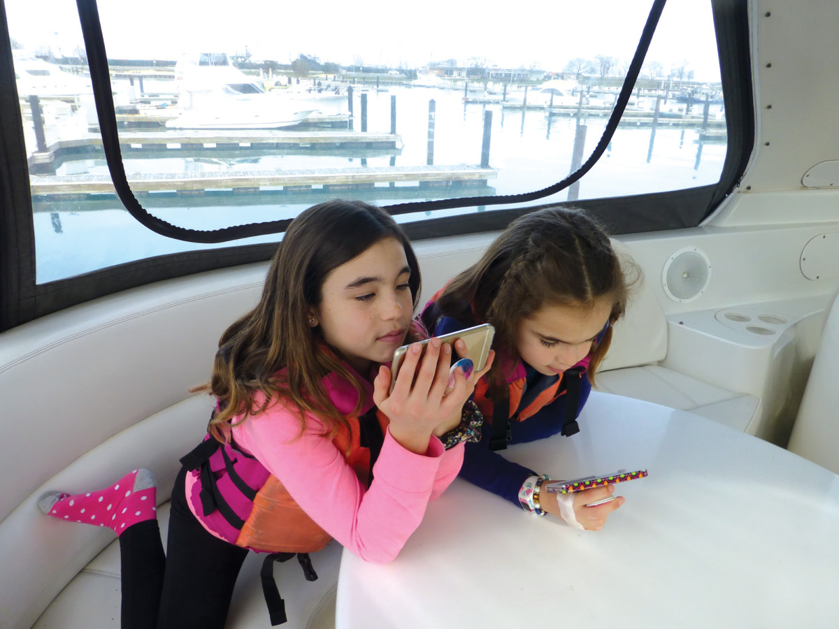 The author's daughters, Molly and Madelyn, were happily connected to YouTube during a 14-month cruise on the family's Carver Voyager 57.
