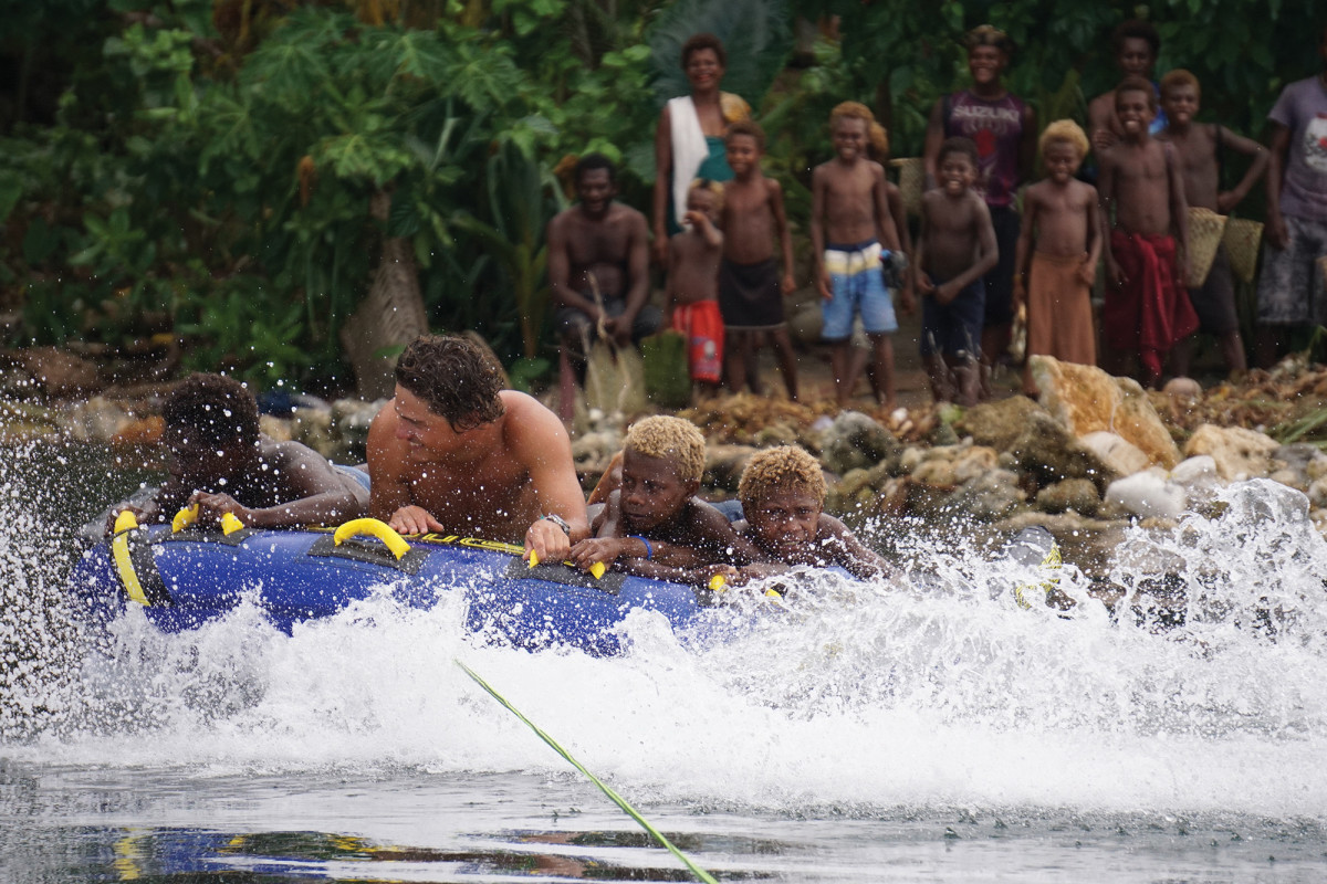 The Reliance crew didn't set out just to circle the world; they set out to see and experience it. Here, Mitch DeVries takes children tubing in Papua New Guinea, a memory he won't soon forget.