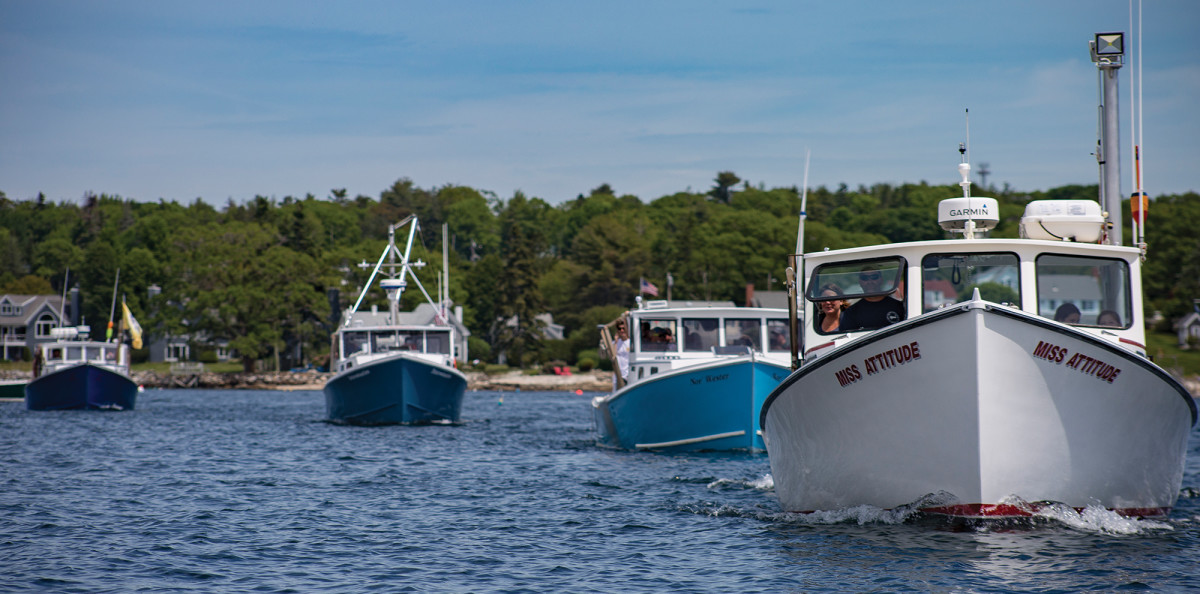 "Lobster boats head to the ""judge's booth""—a floating dock precariously located in the middle of the harbor—after a race."