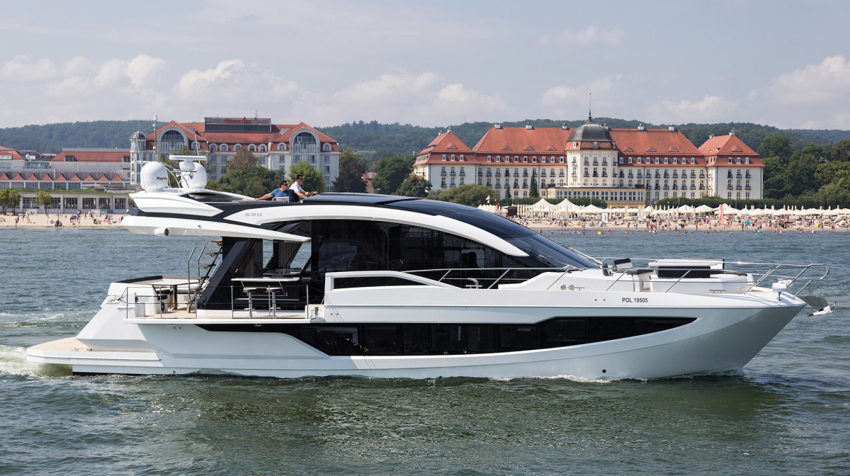 The Galeon 650 Skydeck cruises off the beachfront in the Baltic resort of Sopot. Note the side terrace and carbon top that closes off the flybridge.