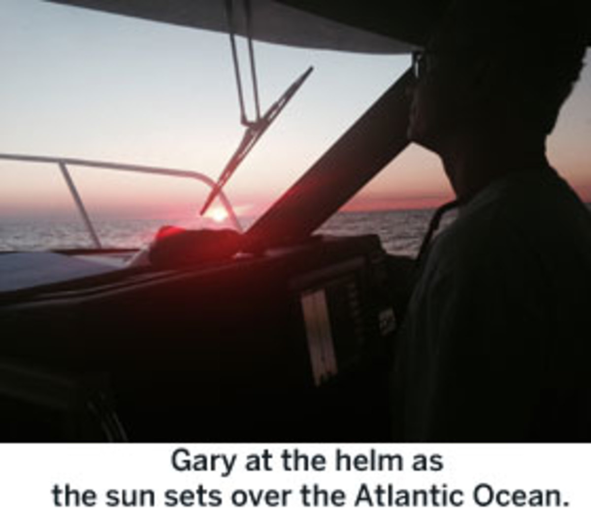 Gary at the helm as the sun sets over the Atlantic Ocean.