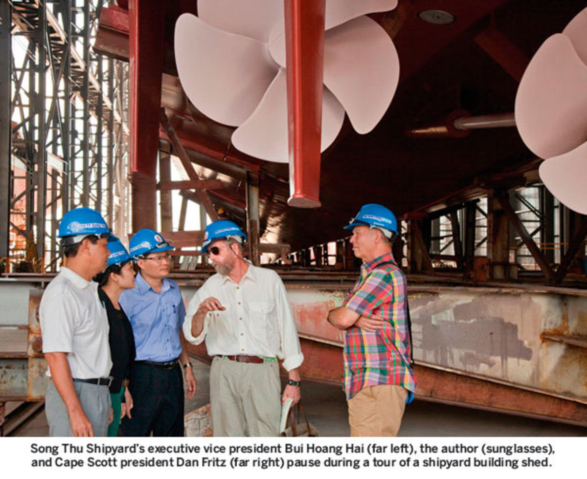 Song Thu Shipyard's executive vice president Bui Hoang Hai (far left), the author (sunglasses), and Cape Scott president Dan Fritz (far right) pause during a tour of a shipyard building shed.