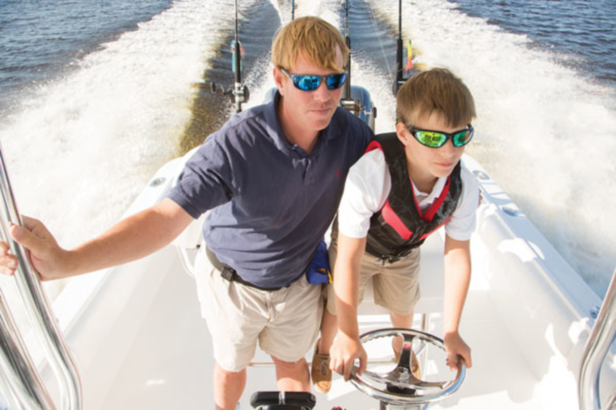 Father and son driving a boat