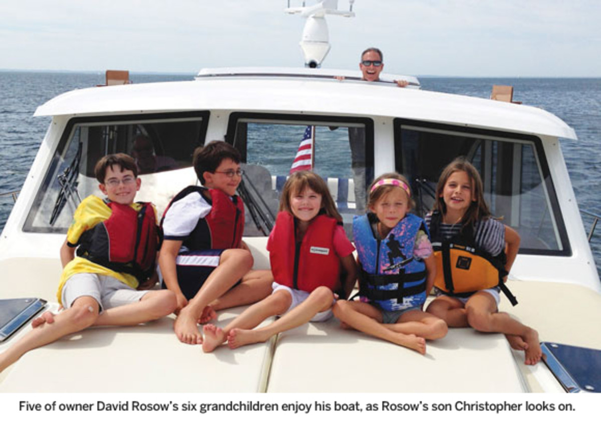 Five of owner David Rosow's six  grandchildren enjoy his boat, as  Rosow's son Christopher looks on.