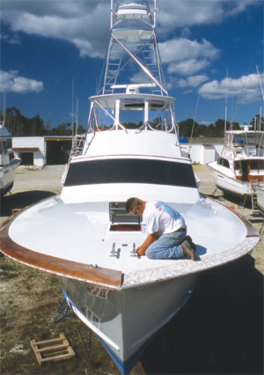 A worker at Jarrett Bay Boatworks spruces up the teak toerail on a sportfisherman.