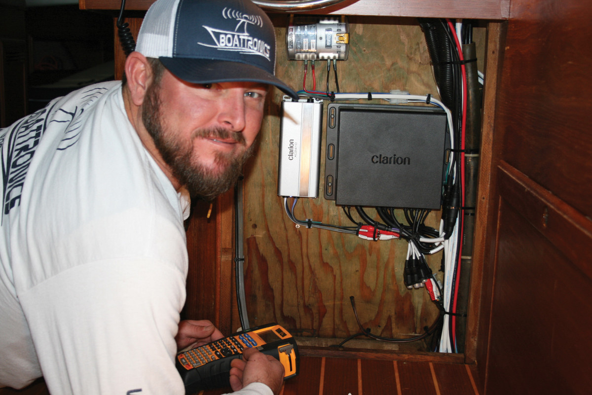 "Tony Eden of Boattronics prints labels for wires. The CMS4's ""Black Box"" and its amplifier are mounted behind a panel at the lower helm."