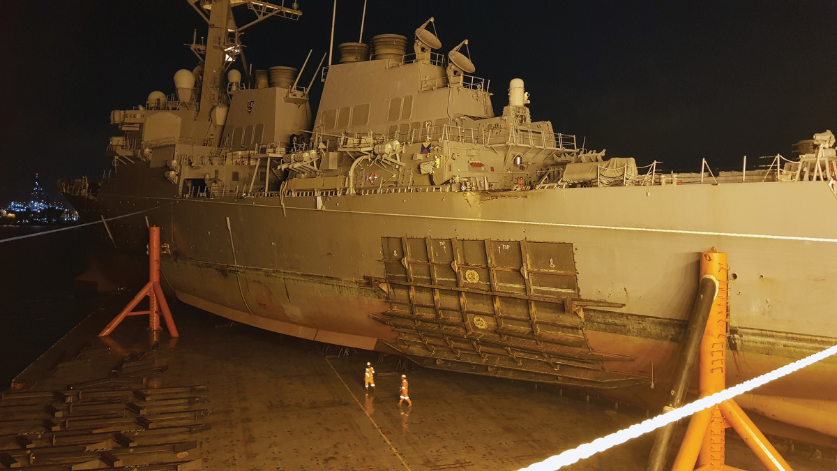 The USS John S. McCain was carefully loaded aboard a heavy-lift transport for transfer to a repair facility in Japan.