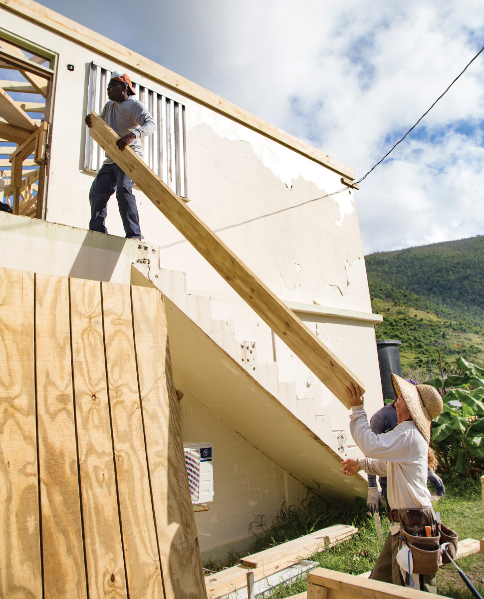 Volunteers work to rebuild the home of the district nurse on Jost Van Dyke, one plank of wood at a time.