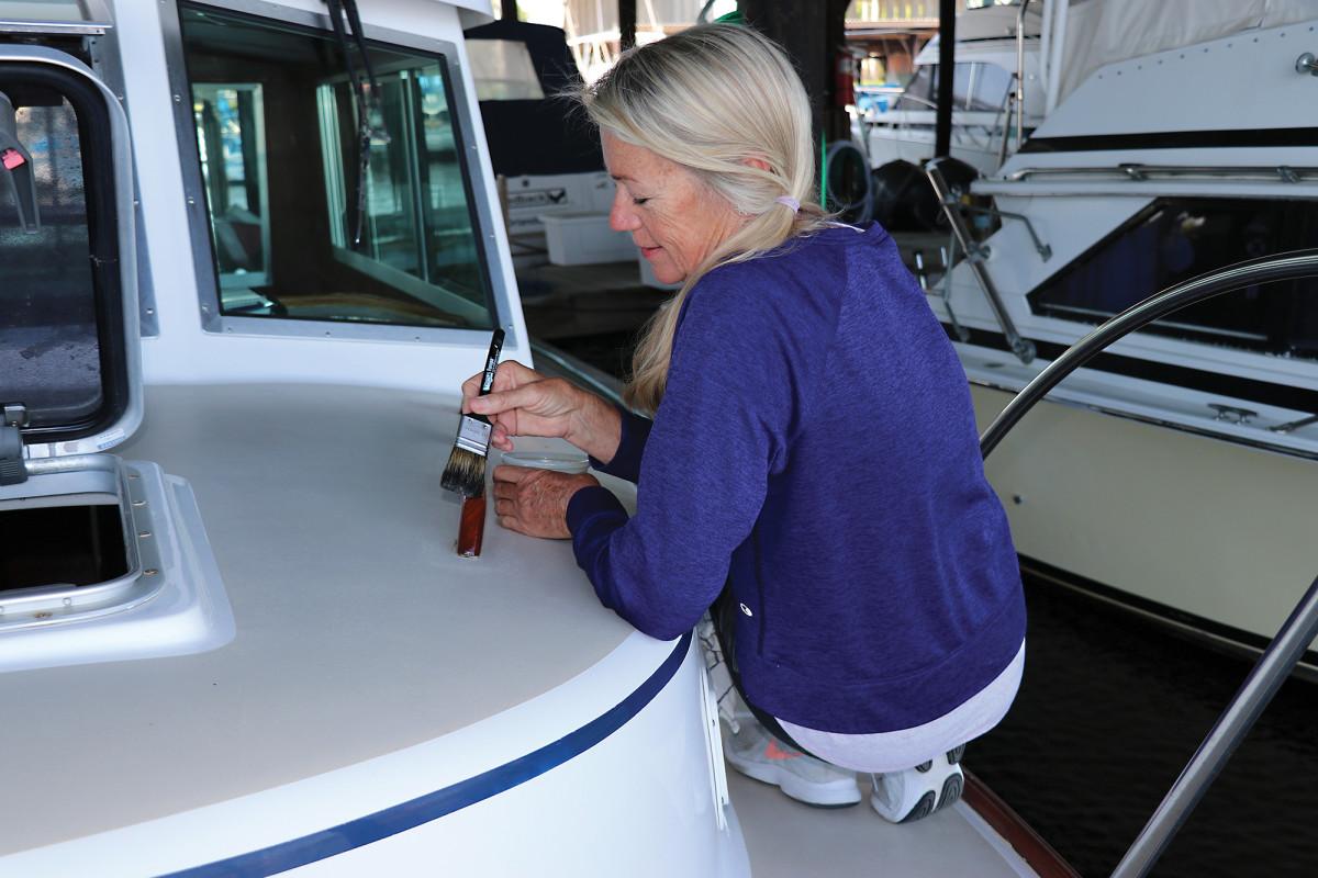 Karen Merkel Schultz varnishes the Betty Jane II the old-fashioned way.