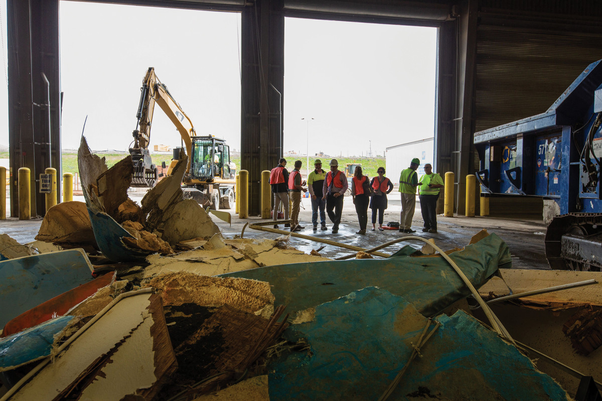 Large fiberglass chunks are crushed into smaller pieces by industrial shredders that will be fed into a cement kiln.