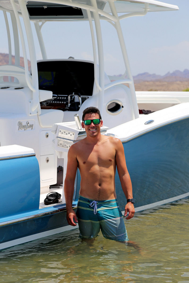 The 30-year-old vice president of Mag Bay Yachts, Barrett Howarth hangs out next to the beached 33 on a sandbar.