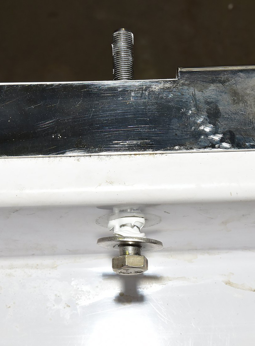 Fender washers inside the transom distribute the strain and provide plenty of surface for bedding compound.