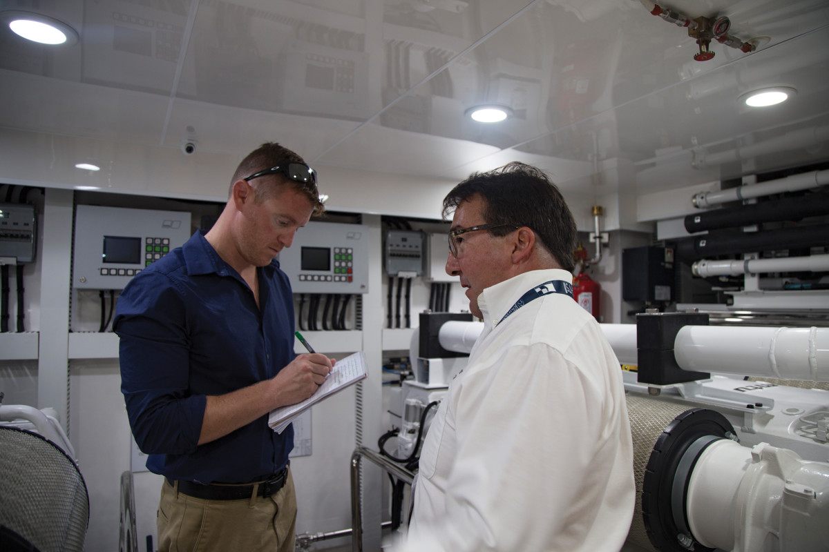The author and Bill Prince inspect an engine room, one of the first things a prospective buyer should do.