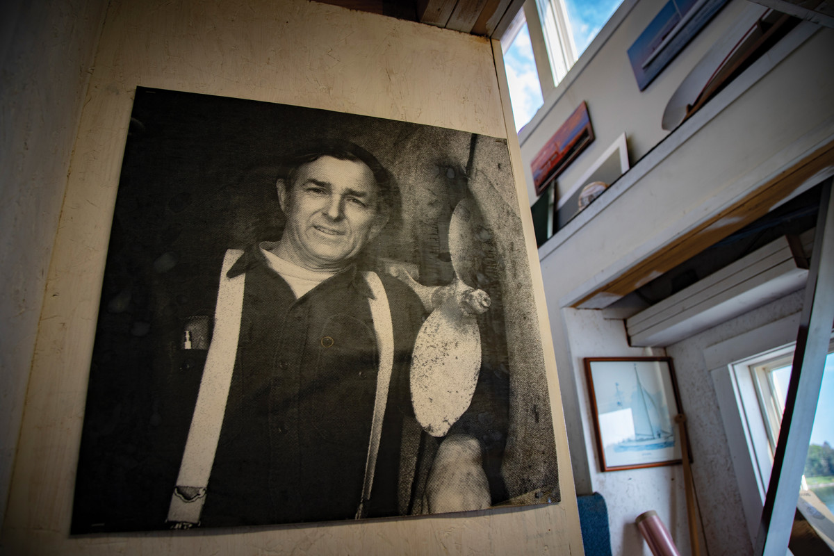 A prominent black-and-white photo of the late Brooklin Boat Yard founder Joel White hangs in the shop.
