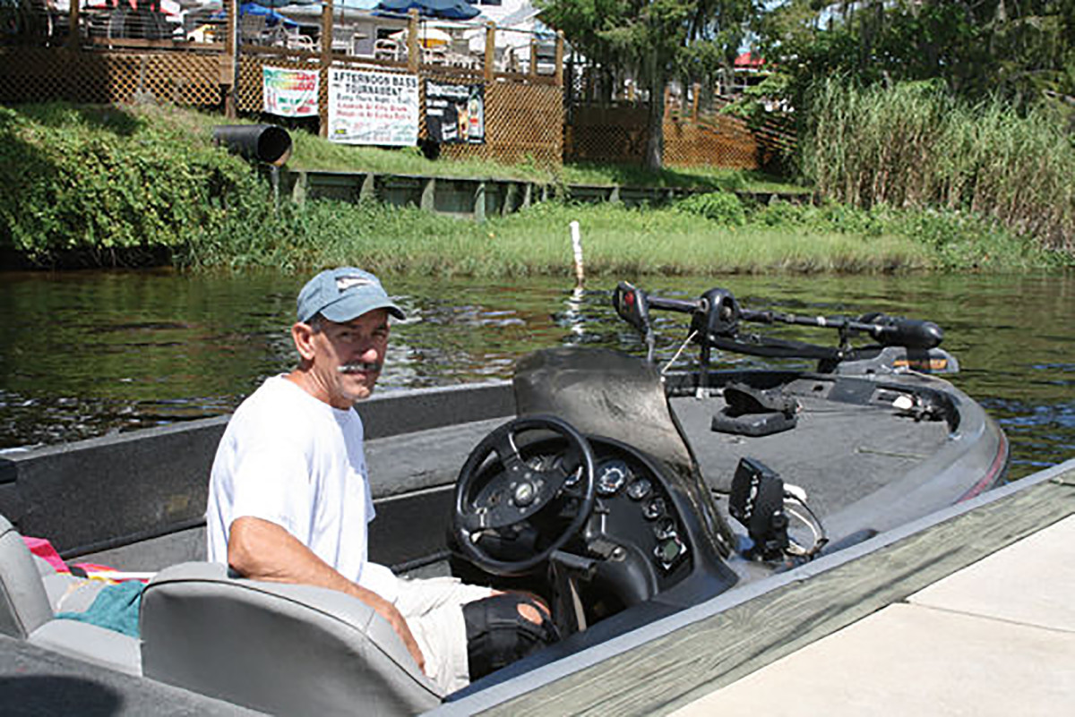 Skip in his bass boat outside of Corky Bell's, where we ate alligator.