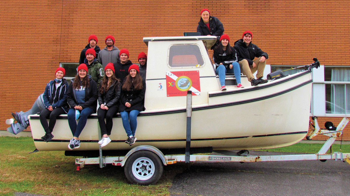 """Jean-Marc Perreault (leaning on hard top) and his students aboard """"La Petite Calypso""""."""