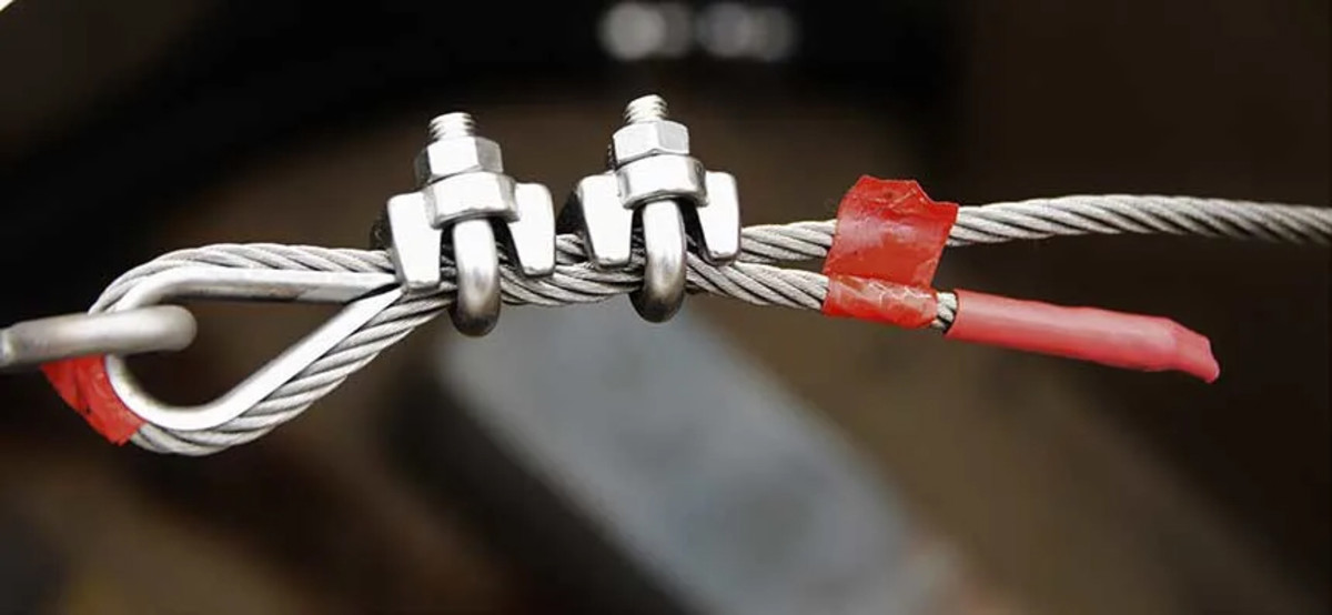 """The """"dead end"""" of the cable has been marked with red tape. The wire clamps consist of a U-bolt and a saddle. These clamps have been installed properly, with the U-bolts on the dead end of the cable and the saddles on the working or standing side of the cable."""