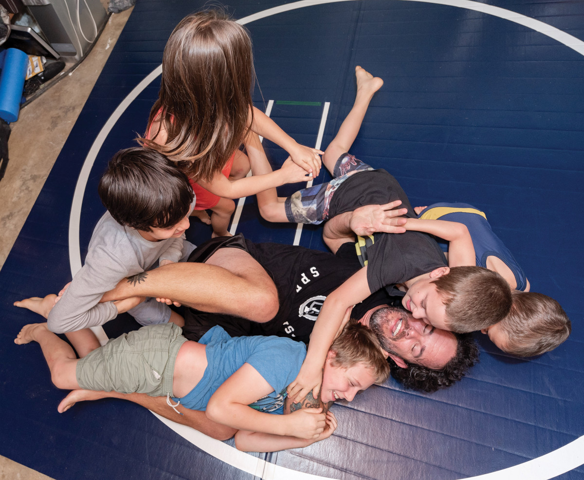 John and five of his seven kids tussling at home.