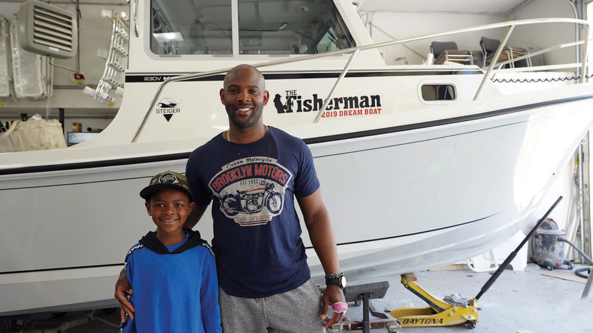 Father and son stand in front of their new Steiger Craft, which Weir won in a fishing competition.